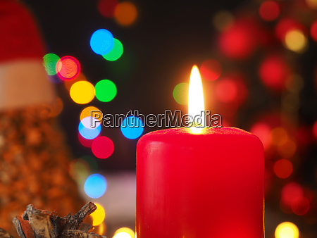 burning advent candle with christmas lights