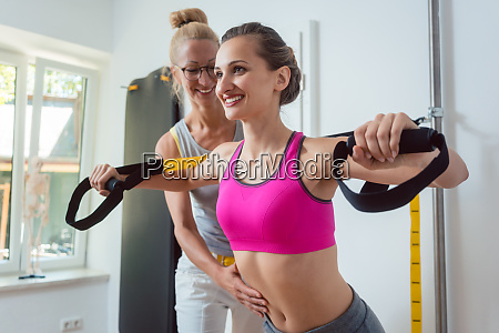 woman using sling trainer during physical