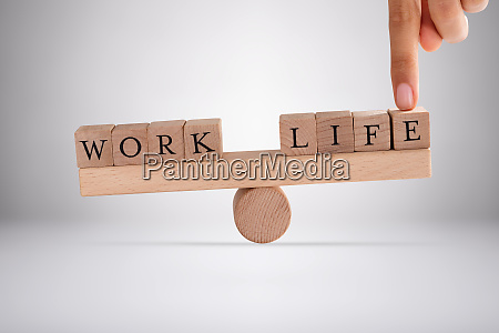persons finger balancing work and life