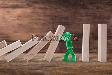 green male figure stopping the domino
