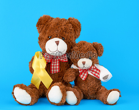 brown teddy bear sits and holds