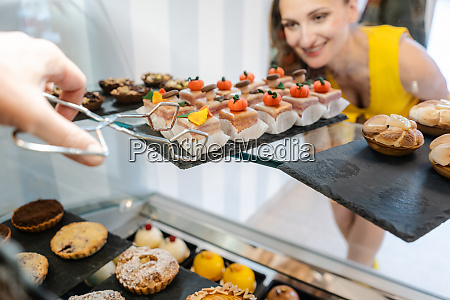 customer woman in confectionery choosing which