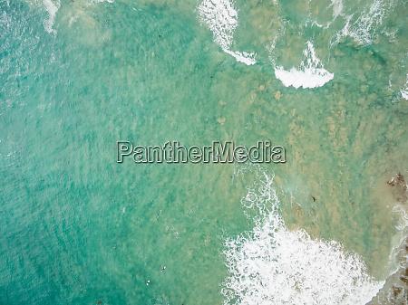 faraway aerial view of people surfing