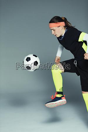 teenage girl soccer player kicking the