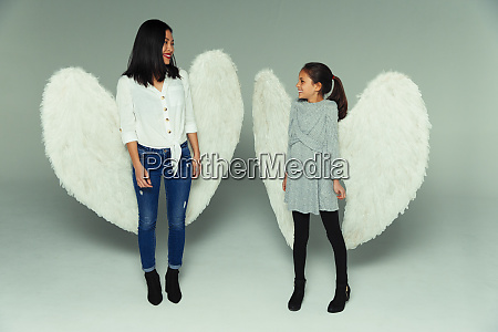 happy mother and daughter wearing angel