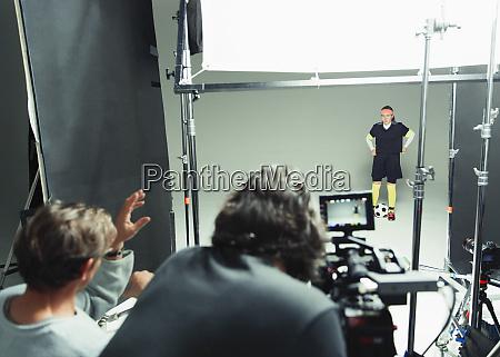 photographers guiding female soccer player model