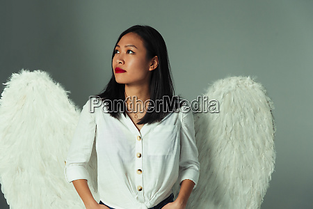serene curious young woman wearing angel