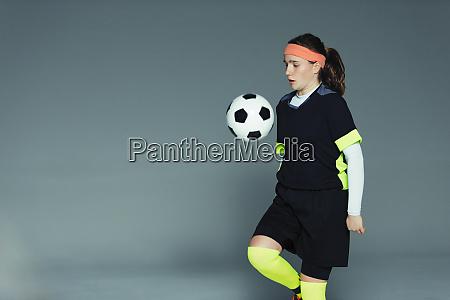 teenage girl soccer player bouncing ball