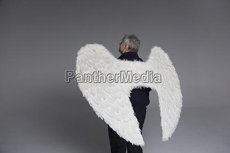 serene man wearing angel wings looking
