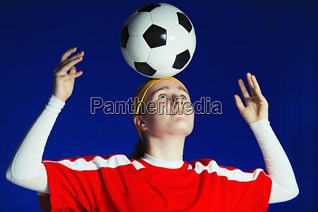 teenage girl soccer player balancing soccer