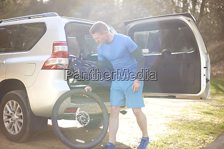 male cyclist removing bike tire from