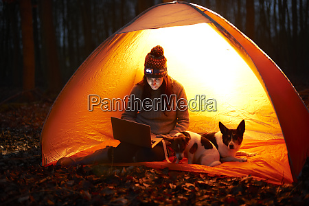 woman with dog using laptop in