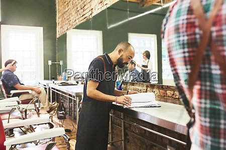 male barber looking at schedule in