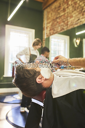 man receiving a shave in barbershop