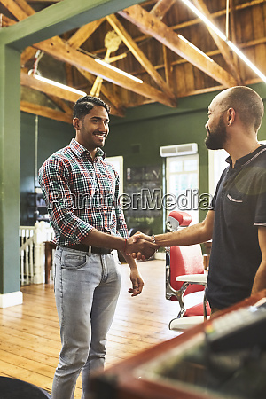 male barber and customer shaking hands