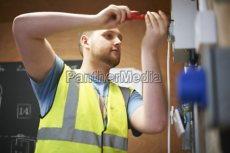 male electrician student using screwdriver