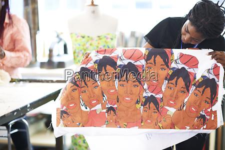 female artist holding screen print in