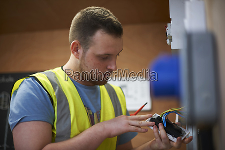 male electrician student examining light switch