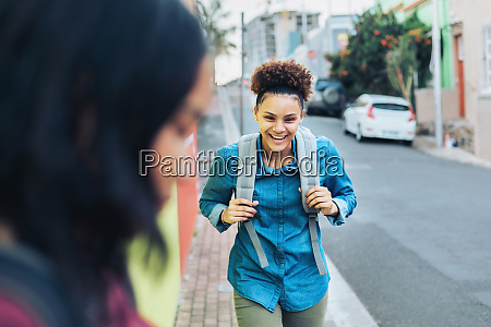 laughing happy young woman with backpack