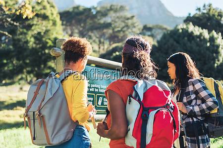 female hikers looking at sign in