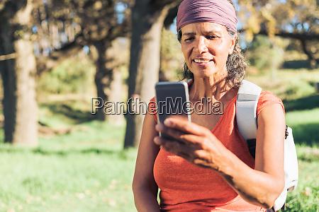 female hiker using smart phone in