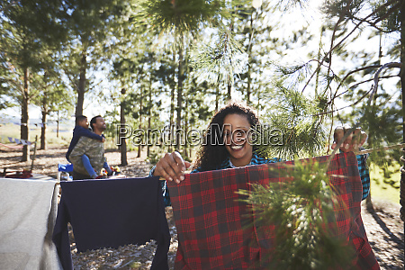 smiling woman hanging clothing on campsite