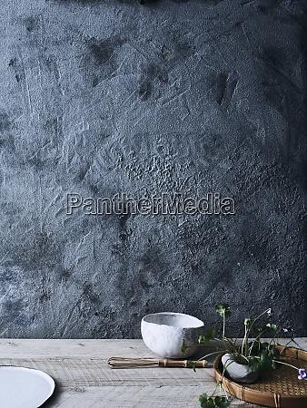 ceramic bowls and plant against background