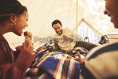 family playing cards inside camping yurt