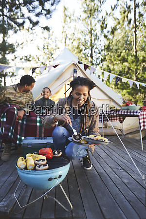 smiling woman cooking vegetables on campsite