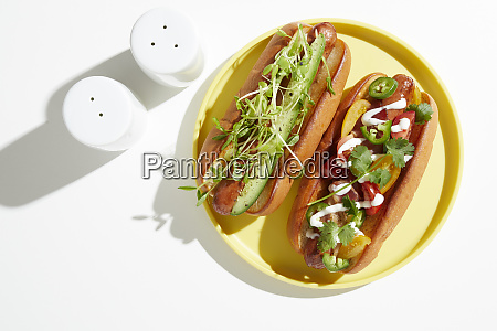 two garnished hotdogs on yellow plate