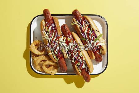 three hotdogs on tray with onion