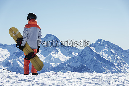teenage boy snowboarder looking out over