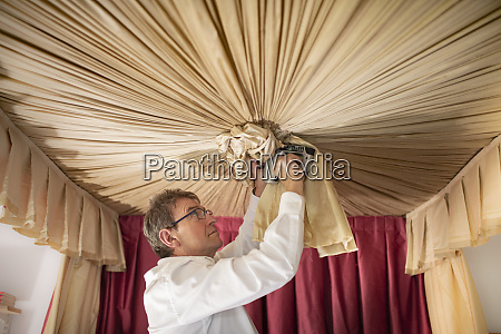 curtain fitter making ruche on canopy