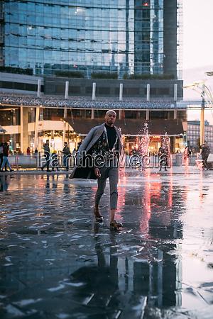 stylish man walking through piazza water