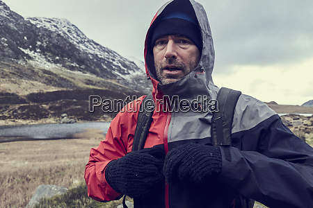 male hiker with hood up in