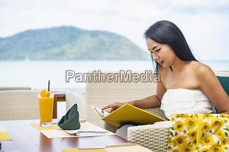 woman reading menu at seaside resort