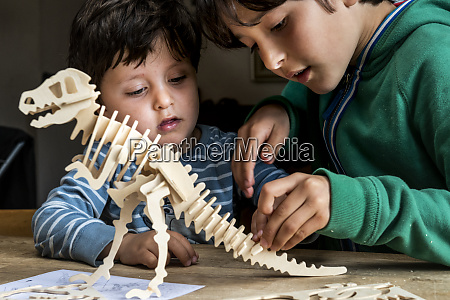 boy showing brother way to build