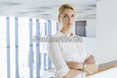 businesswoman taking break in office corridor