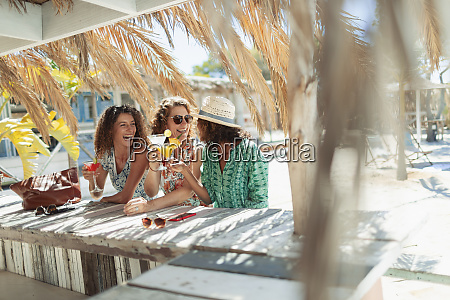 happy women drinking cocktails at sunny