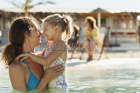happy affectionate mother and daughter swimming