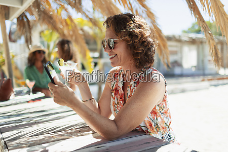carefree woman drinking cocktail and using