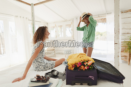 young women friends unpacking suitcase in