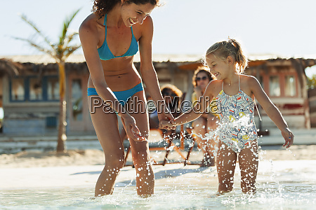 playful mother and daughter splashing in