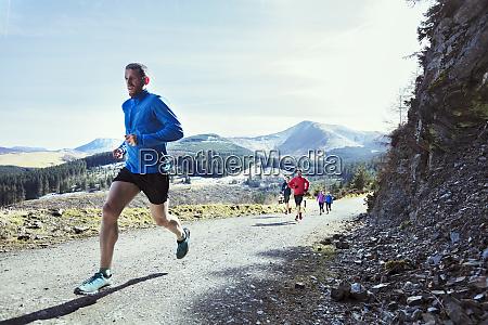 friends jogging on mountain trail