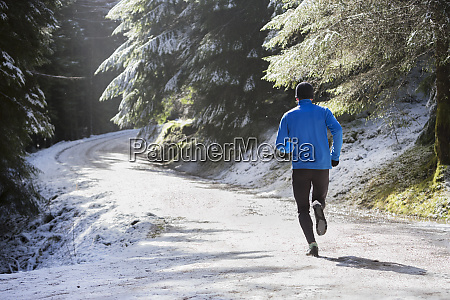 man jogging in snowy woods