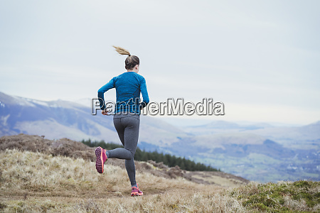 woman jogging on mountain trail