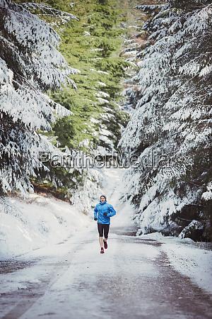 man jogging in snowy woods