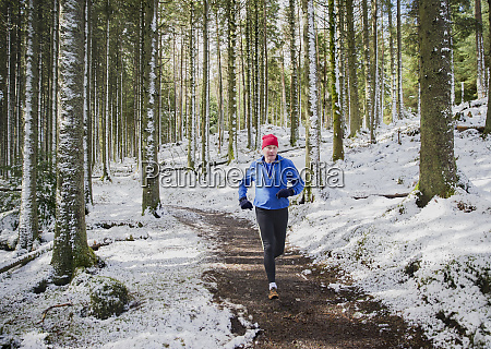 senior man jogging in snowy woods