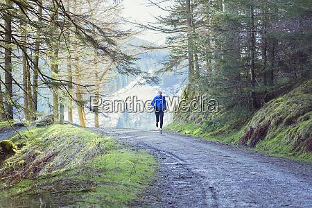 senior man jogging in woods