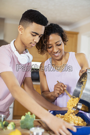 mother and teenage son cooking in